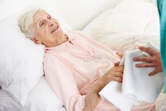 Seniorin wird von Pflegekraft im Bett gewaschen